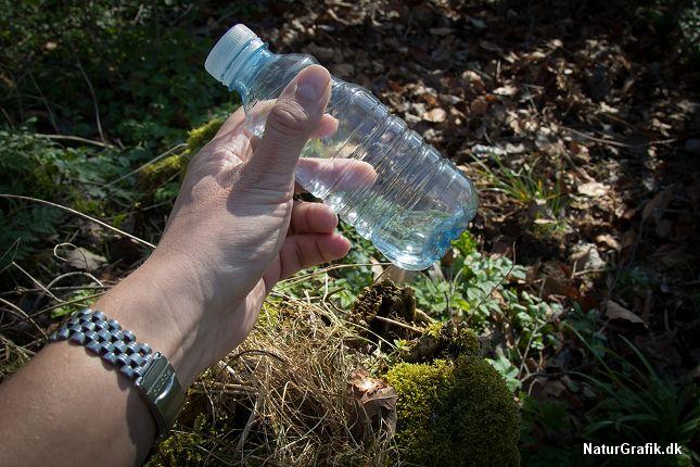 En klar vandflaske med vand, kan bruges som brændglas.